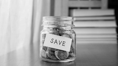 "A jar full of coins with a label ""Save"" illustrating that teams may not always need more money and resources"